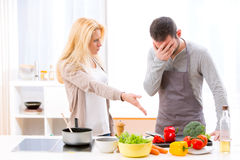 Young attractive couple having an argue while cooking. View of a Young attractive couple having an argue while cooking Royalty Free Stock Photography
