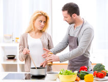 Young attractive couple having an argue while cooking Royalty Free Stock Photos