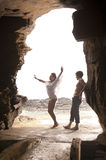 Young attractive couple having dancing through rock archway. At the beach Royalty Free Stock Photography