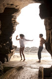 Young attractive couple having dancing through rock archway. At the beach Stock Photo