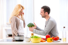 Young attractive couple having fun in the kitchen Stock Images