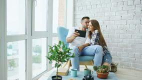 Young attractive couple having online video chat using tablet computer sitting at balcony in modern loft apartment Royalty Free Stock Image