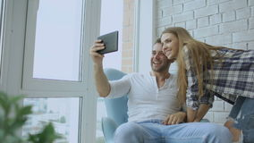 Young attractive couple having online video chat using tablet computer sitting at balcony in modern loft apartment stock footage