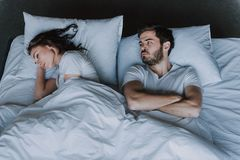 Young Attractive Couple Having Problem in Bed royalty free stock image
