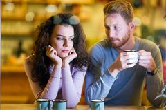 Young attractive couple having problems on date stock images