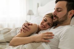 Young attractive couple having romantic time in bed stock image