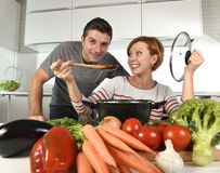 Young attractive couple at home kitchen with man tasting vegetable stew cooked by her wife smiling happy Royalty Free Stock Image