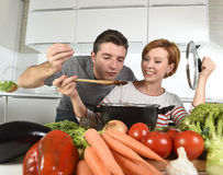 Young attractive couple at home kitchen with man tasting vegetable stew cooked by her wife smiling happy Stock Images