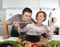 Young attractive couple at home kitchen with man tasting vegetable stew cooked by her wife smiling happy Stock Photos