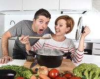 Young attractive couple at home kitchen with man tasting vegetable stew cooked by her wife smiling happy Royalty Free Stock Images