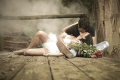 Young attractive couple kissing on wooden deck in forest. With bunch of roses Royalty Free Stock Photography