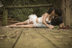 Young attractive couple kissing on wooden deck in forest. With bunch of roses Stock Image