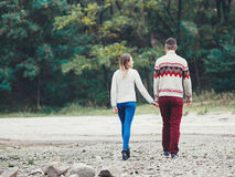 Young attractive couple in knitted sweaters on a cliff on sea shore Stock Images