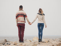 Young attractive couple in knitted sweaters on a cliff on sea shore, Royalty Free Stock Photos