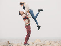 Young attractive couple in knitted sweaters on a cliff on sea shore Royalty Free Stock Photos
