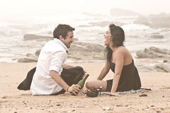 Young attractive couple laughing on beach. With wine bottle Stock Photography