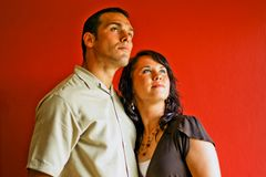 Young Attractive Couple Looking. Male and female looking out into the distance against a red background Stock Photos