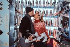 Young couple in love, kiss while standing near rack with many pairs of skates. Young attractive couple in love, kiss while standing near rack with many pairs of stock image