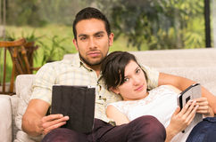 Young attractive couple lying in the sofa using Royalty Free Stock Photo