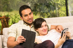 Young attractive couple lying in the sofa using Stock Images