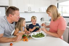 Young attractive couple mother and father preparing salad together with little son and young beautiful daughter in healthy vegetab