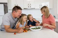 Young attractive couple mother and father preparing salad together with little son and young beautiful daughter in healthy vegetab Royalty Free Stock Photos