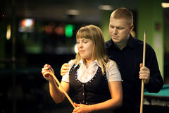 The young attractive couple plays billiards. Young attractive couple plays billiards stock image