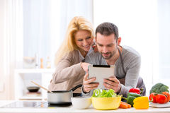 Young attractive couple reading recipe on a  tablet Royalty Free Stock Images