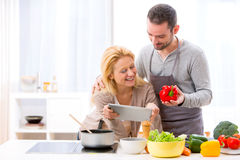 Young attractive couple reading recipe on a  tablet Stock Photography
