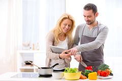 Young attractive couple reading recipe on a  tablet Stock Photo