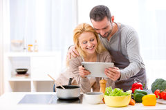 Young attractive couple reading recipe on a  tablet Stock Image