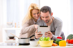 Young attractive couple reading recipe on a  tablet Royalty Free Stock Photos