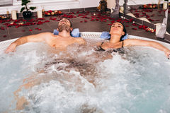 Young attractive couple relax in hot tub. In spa center stock image