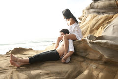 Young attractive couple relaxing outdoors on beach rocks Royalty Free Stock Photography