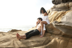 Young attractive couple relaxing outdoors on beach rocks Stock Photography