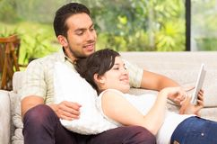 Young attractive couple relaxing in the sofa using Royalty Free Stock Photography