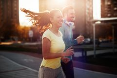 Young attractive couple running outside on sunny day Stock Photos