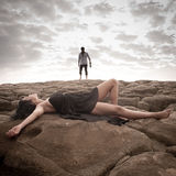 Young attractive couple sharing a moment outdoors on beach rocks. With cloudy skies above them Royalty Free Stock Images
