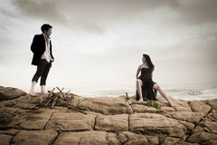 Young attractive couple sharing a moment outdoors on beach rocks. With fire wood Stock Photo