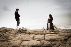 Young attractive couple sharing a moment outdoors on beach rocks. With fire wood Royalty Free Stock Photography