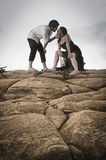 Young attractive couple sharing a moment outdoors on beach rocks Stock Photos