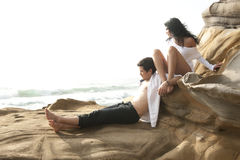 Young attractive couple sharing a moment outdoors on beach rocks Royalty Free Stock Photos