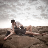 Young attractive couple sharing a moment outdoors on beach rocks. With wine bottle Stock Photography