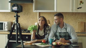 Young attractive couple shooting video food blog about cooking on dslr camera in the kitchen stock video footage
