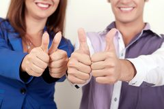 Young attractive couple showing thumbs up.  Stock Images