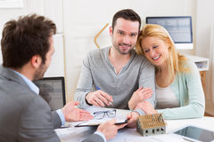 Young attractive couple signing contract with real estate agent Stock Photography