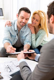 Young attractive couple signing contract with real estate agent Royalty Free Stock Images