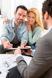 Young attractive couple signing contract with real estate agent Royalty Free Stock Image