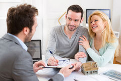 Young attractive couple signing contract with real estate agent Stock Image