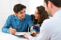 Young attractive couple signing contract Royalty Free Stock Photography